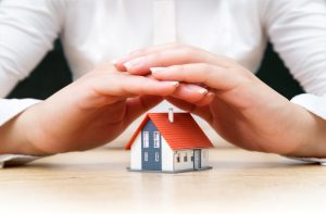 house covered of woman hands - insurance real estate concept
